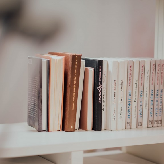 A photo of books stacked upright on top of a white shelf