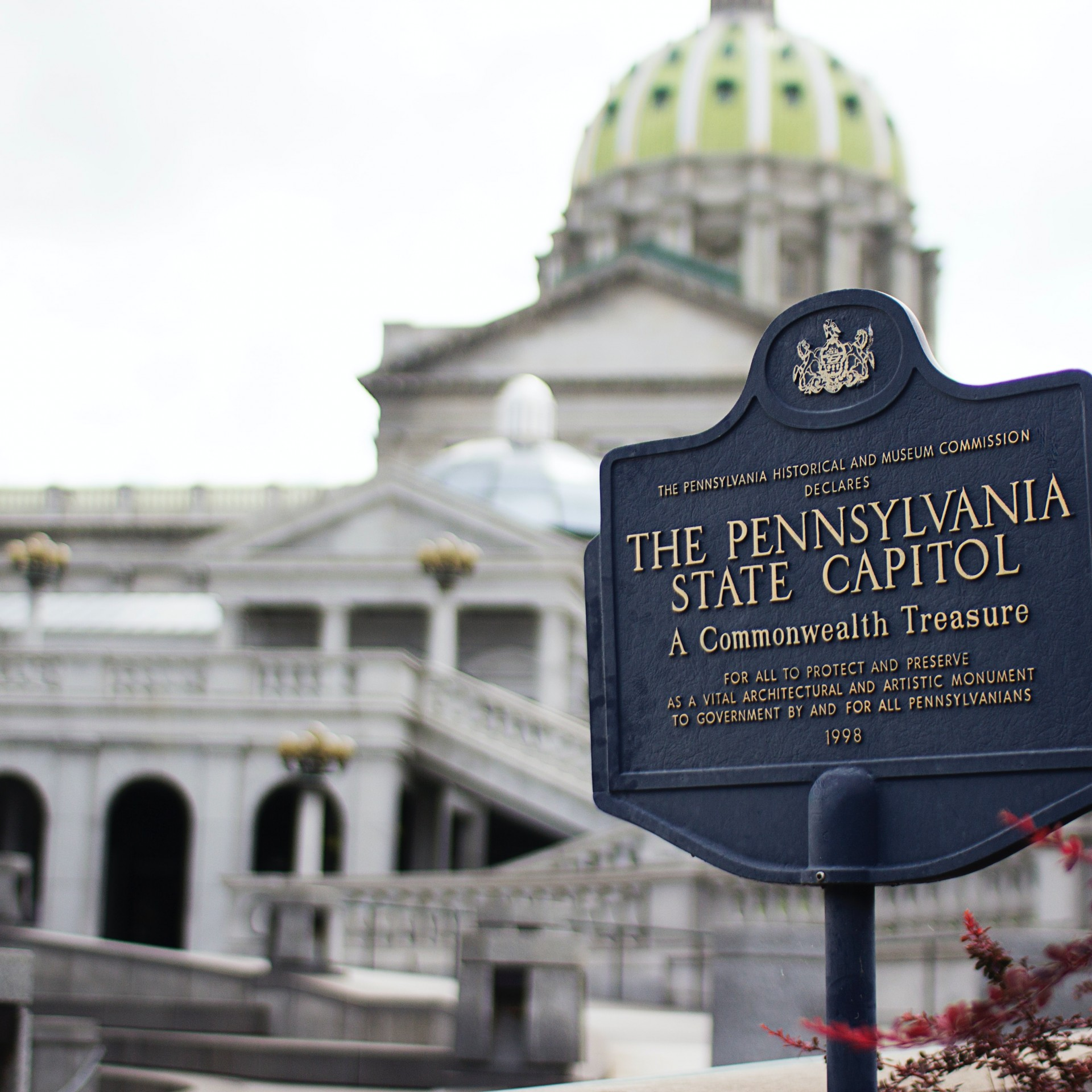 Exterior image of the Pennsylvania State Captial and a sign announing the building in foreground